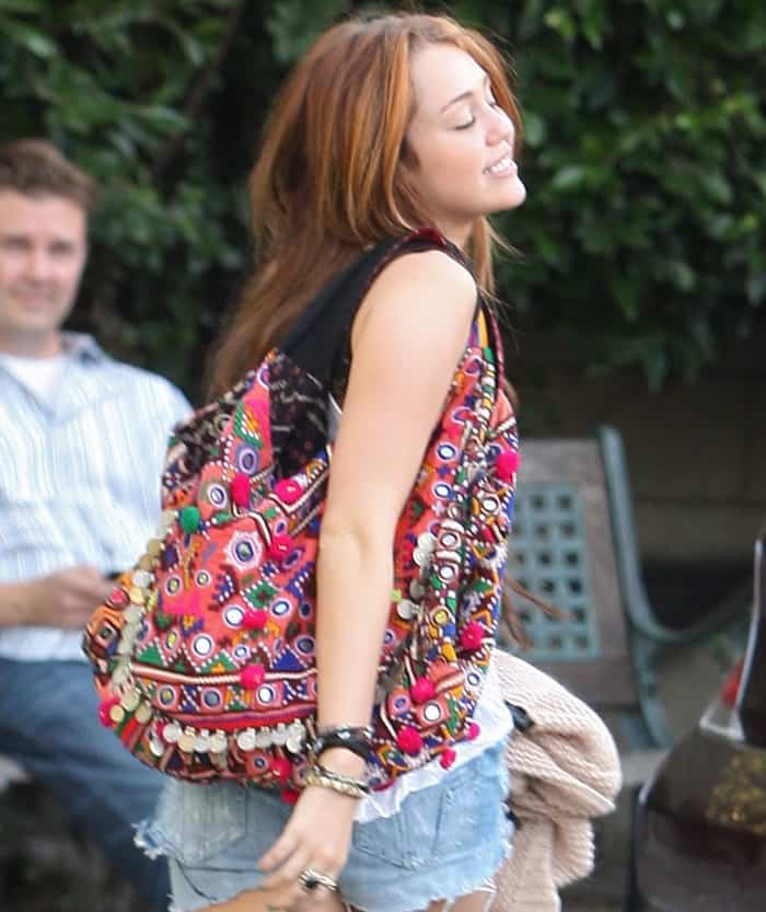 e54068636e24 Miley Cyrus Loves Her Super Colorful Mirror and Pompom Bag