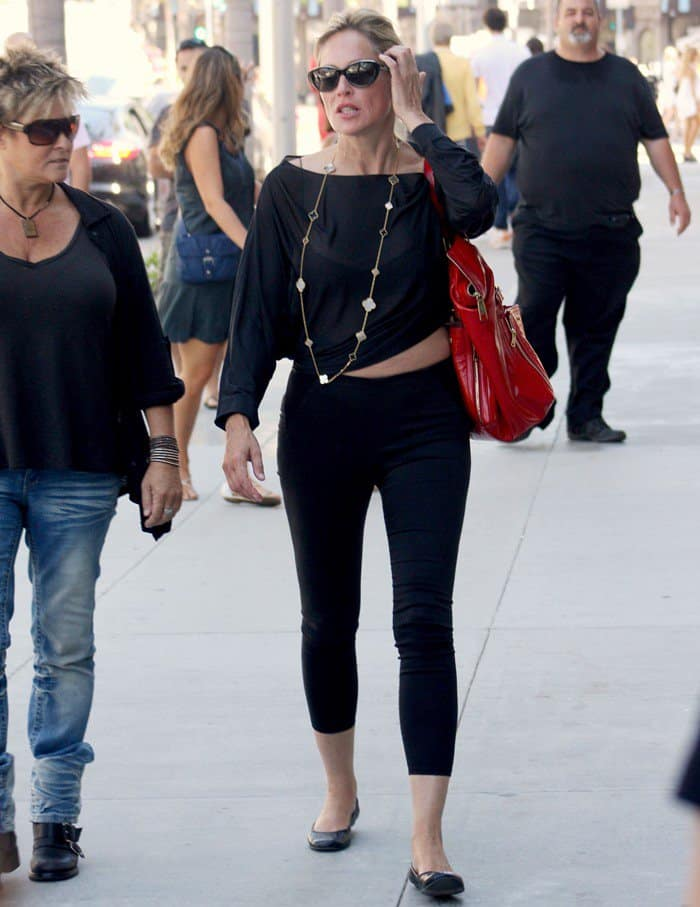 Sharon Stone added color to her all-black outfit with a red patent purse