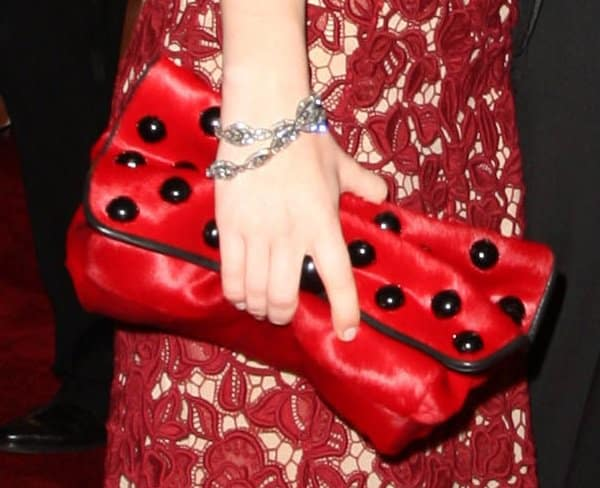 Emily Browning toted a red and black polka dot clutch