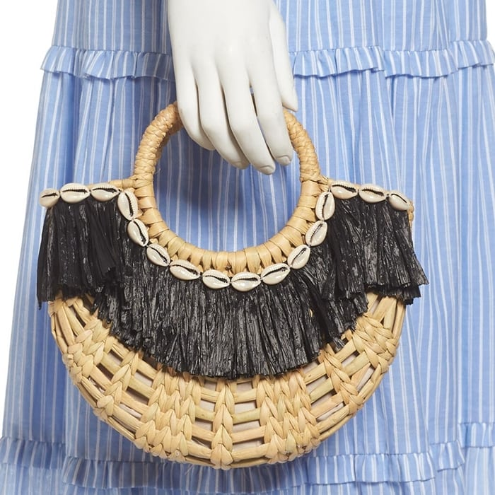 Cowrie shell and raffia trim add fun, festive touches to a woven straw handbag that channels carefree vacation vibes