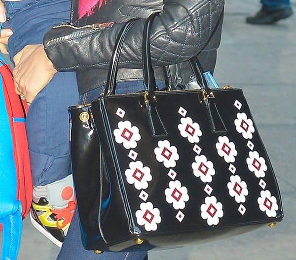 Miranda Kerr's Prada floral applique Spazzolato bag on the other