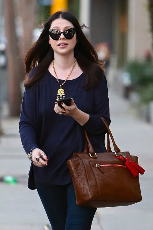 Michelle Trachtenberg carrying a Coach handbag and wearing a Chanel necklace