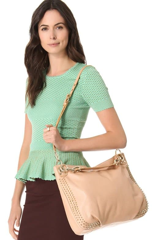 A swath of studs bristles around the edges of a slim hobo shaped from supple leather