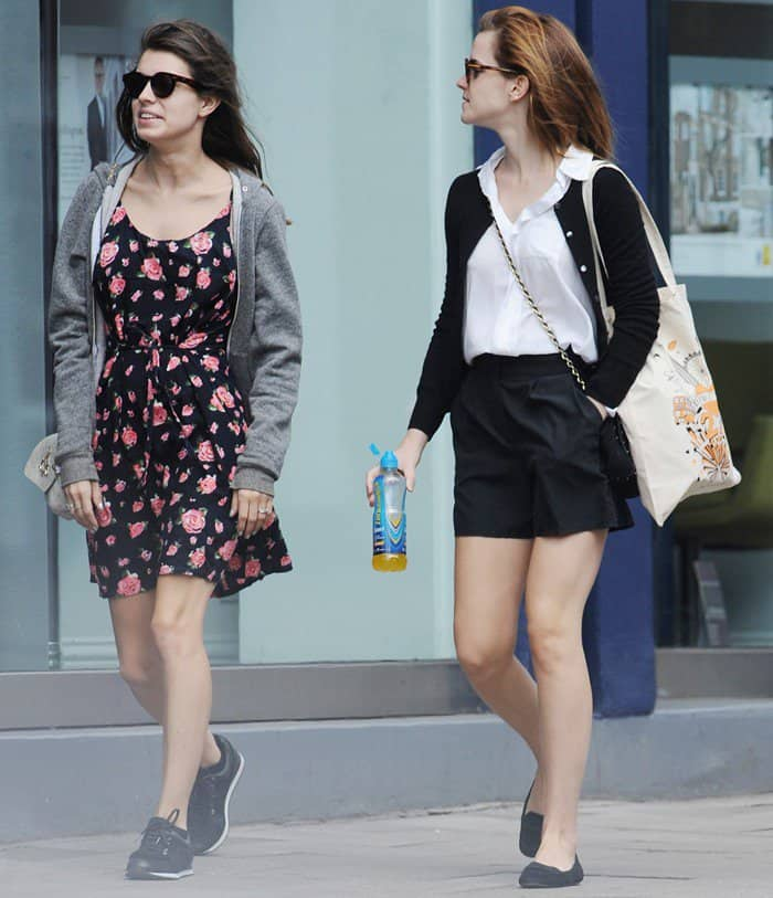 Emma Watson takes advantage of the spring sunshine in the U.K. and shows off her legs in black shorts as she and a friend stroll through West London