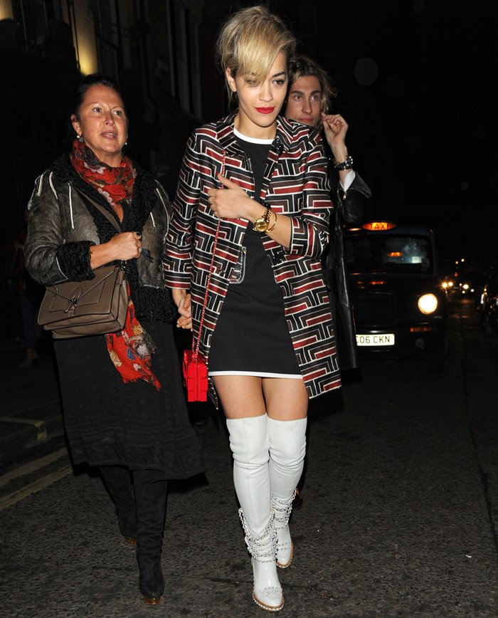 Rita Ora wearing a printed coat, an LBD, white over-the-knee boots, and a striking red box clutch with intertwining Cs on it