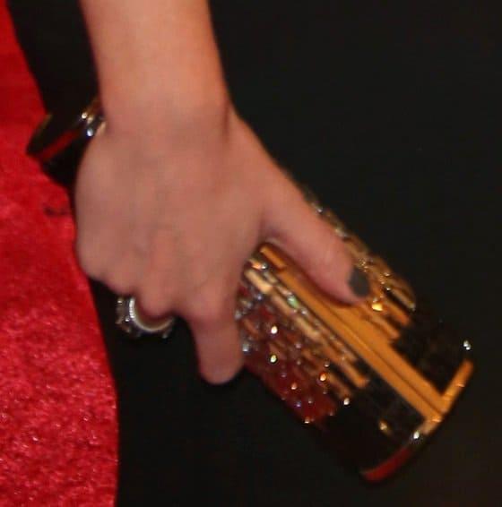 Emily Blunt toting gold barrel clutch