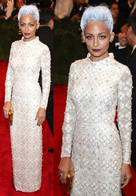 Nicole Richie showing off a megasized ruby ring plus a glam gold clutch from her own collection