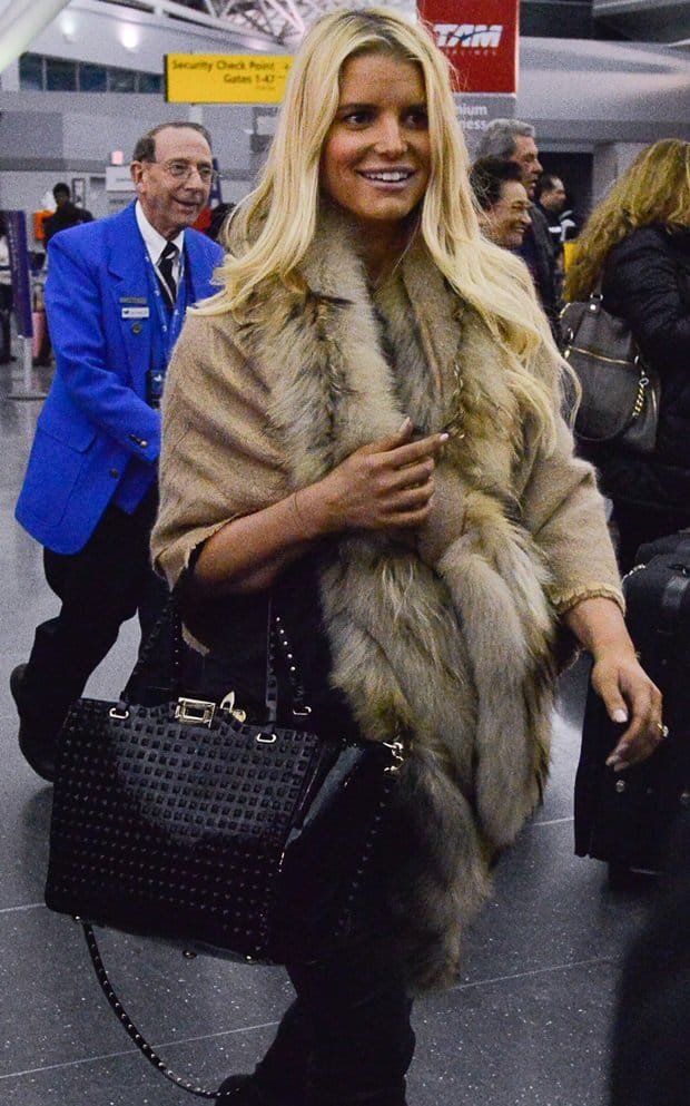 Jessica Simpson wears a faux-fur-trimmed shawl at JFK airport