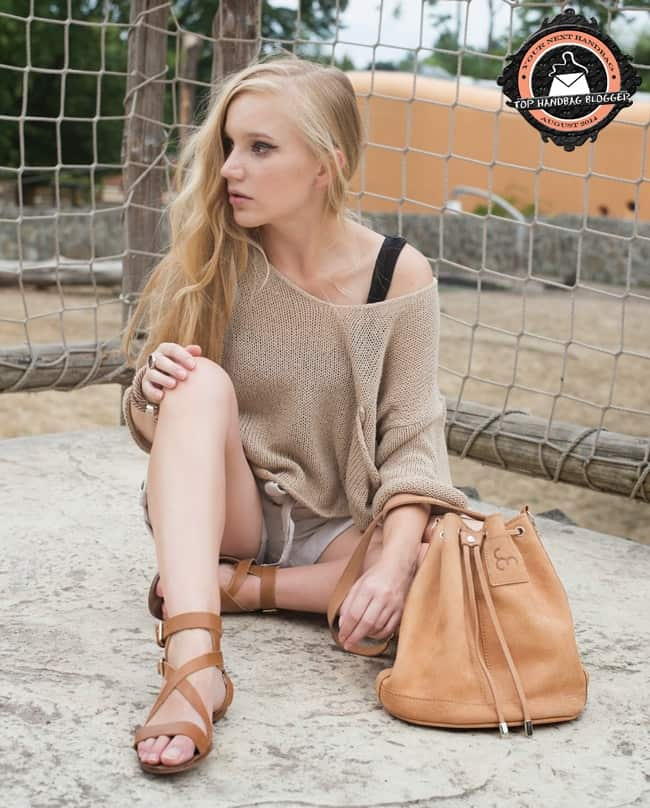Ewa rocks a chunky sweater with linen shorts, strappy flat sandals, and a rope-like bracelet
