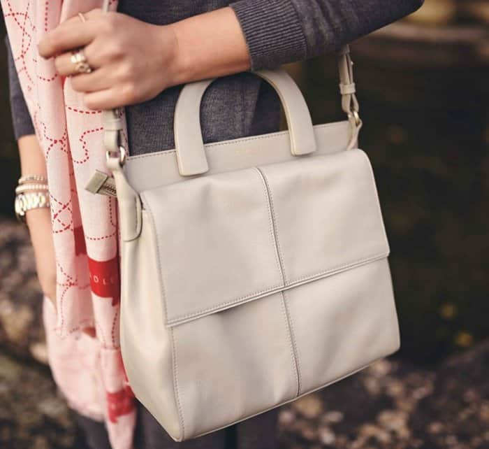 Elena's white handbag features an abundance of compartments