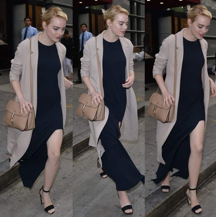 Emma Stone wears a navy dress layered under a nude color trench coat