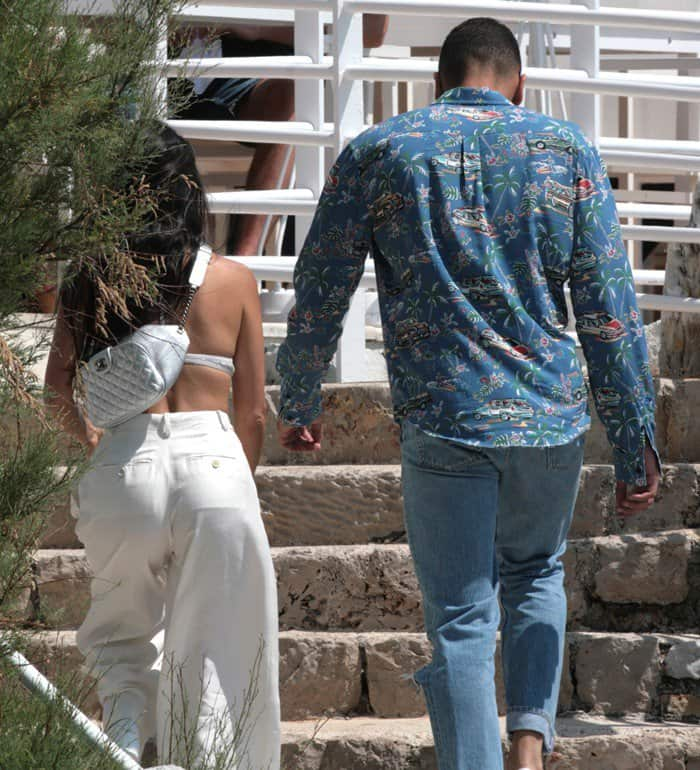 Kourtney Kardashian in a white bralette-and-pants ensemble