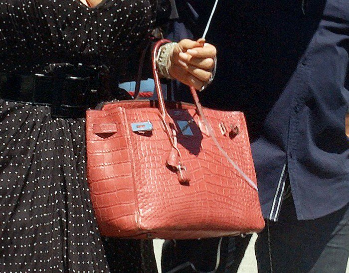 Mariah Carey styled her polka dot dress with a stunning red crocodile Hermes Birkin bag.