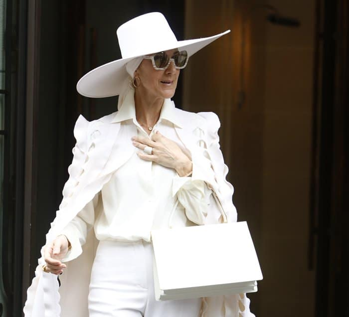 Celine Dion carries a white Celine Medium Clasp Tote during Paris Fashion Week.