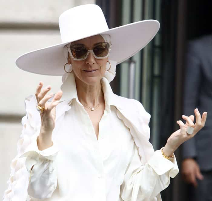 Celine Dion styled her all-white look with a large fedora hat and vintage sunglasses.