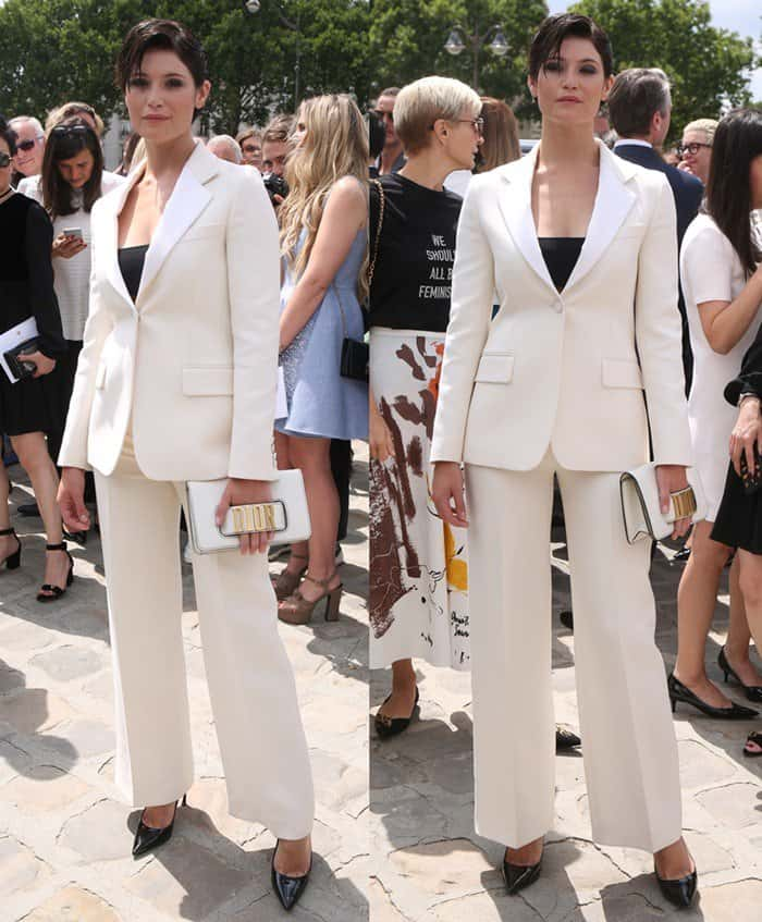 Gemma Arterton wearing a chic white suit ensemble at the Dior fashion show during Paris Fashion Week.