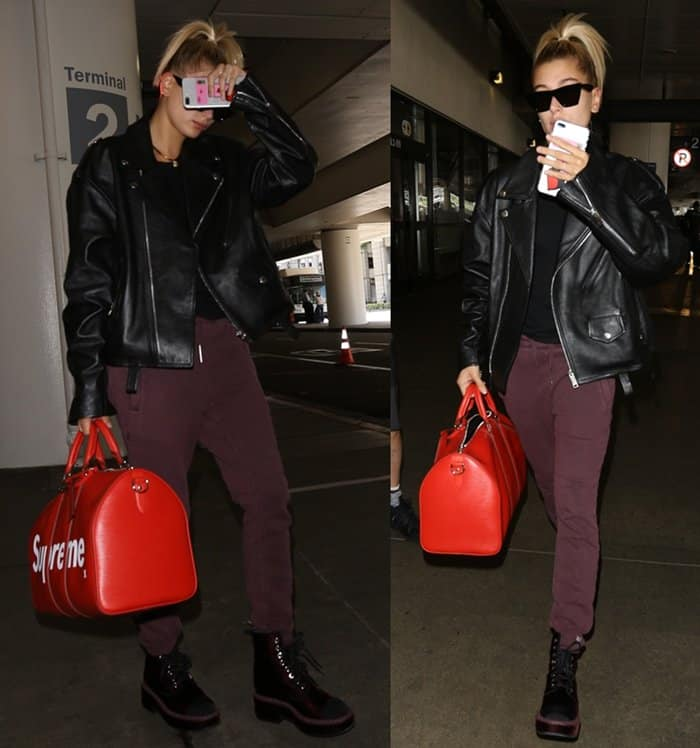 Hailey Baldwin wearing an urban casual outfit comprised of mixed black and wine-colored pieces
