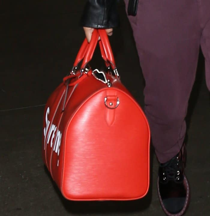Hailey Baldwin carrying a red Louis Vuitton tote at the airport.
