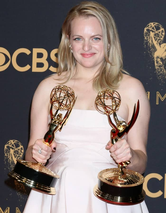 Elisabeth Moss poses with two Emmy trophies on the red carpet.