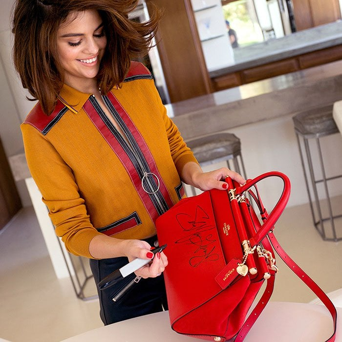 Coach endorser Selena Gomez signs a bag to give away to fans