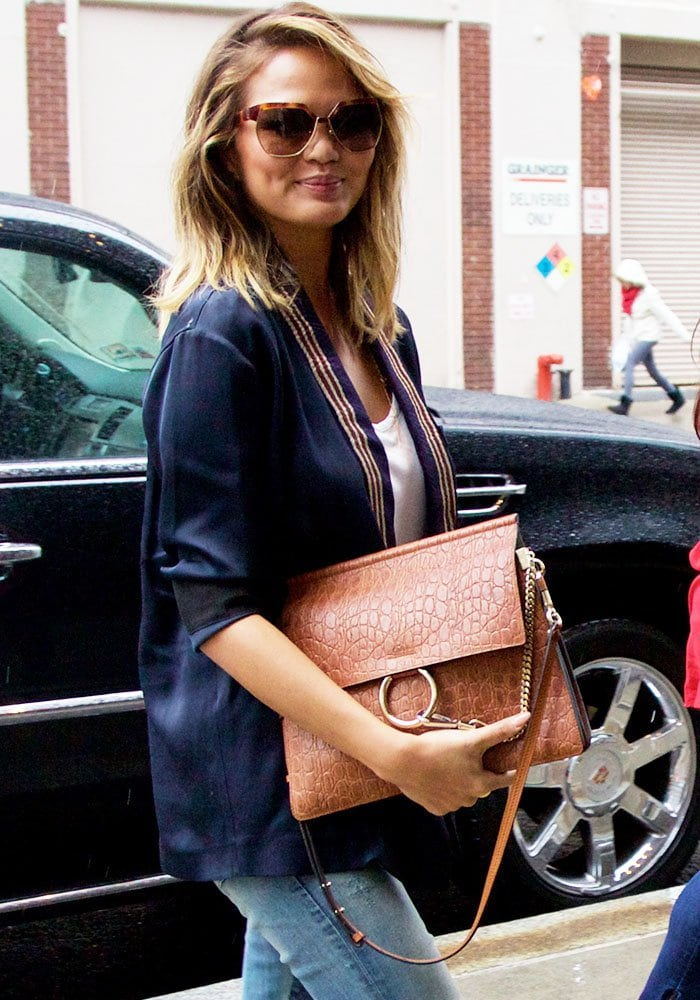 Chrissy Teigen toting her favorite Coach handbag