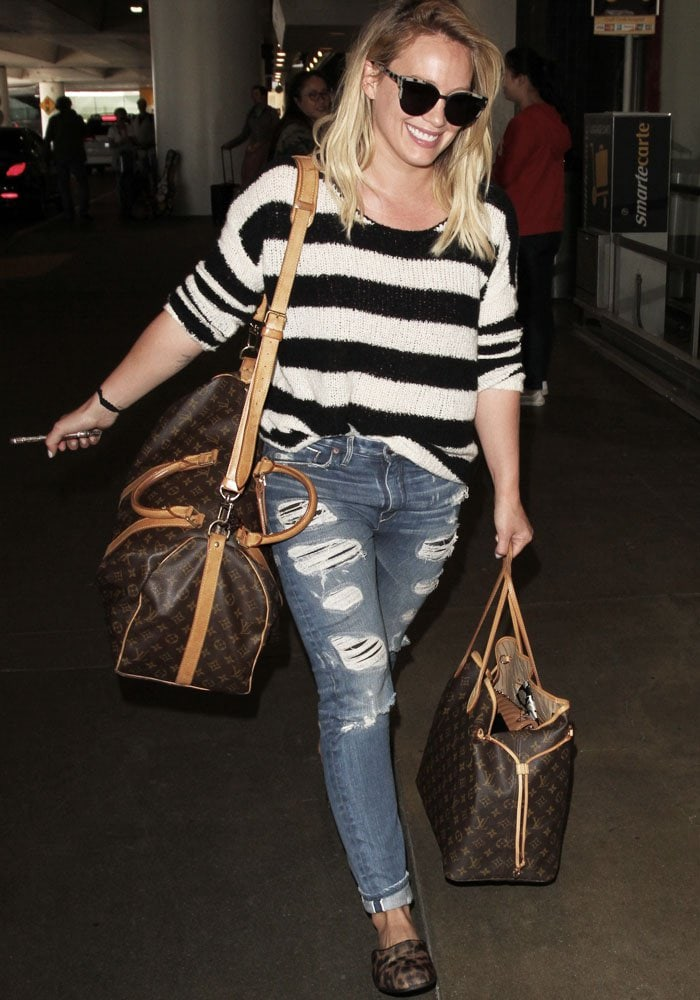 Hilary Duff gleefully strolls through the Los Angeles Airport (LAX) with her two-piece Louis Vuitton luggage