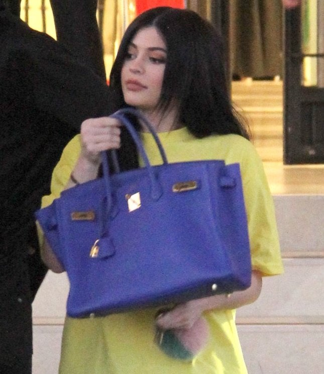 Kylie Jenner holds up her blue Hermès Birkin bag while shopping at Barneys New York in 2016