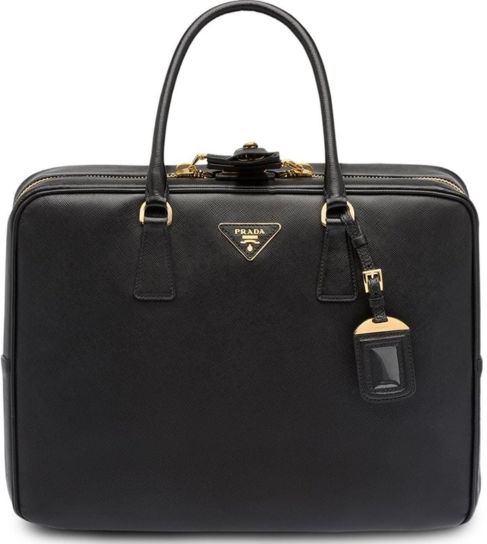 A prime example of traditional Milanese craftsmanship is this black Saffiano leather logo suitcase from Prada featuring top handles, a two-way zip fastening, a front logo plaque, gold-tone hardware, multiple interior compartments, a hanging leather tag, and a sleep mask with pouch