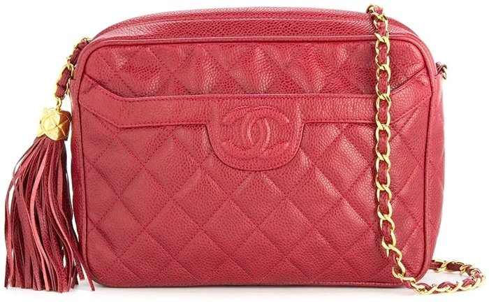Fabricated from diamond quilted caviar leather in lovely red with enriched gold-toned hardware, this camera bag is a Chanel classic with its hanging charming tassel