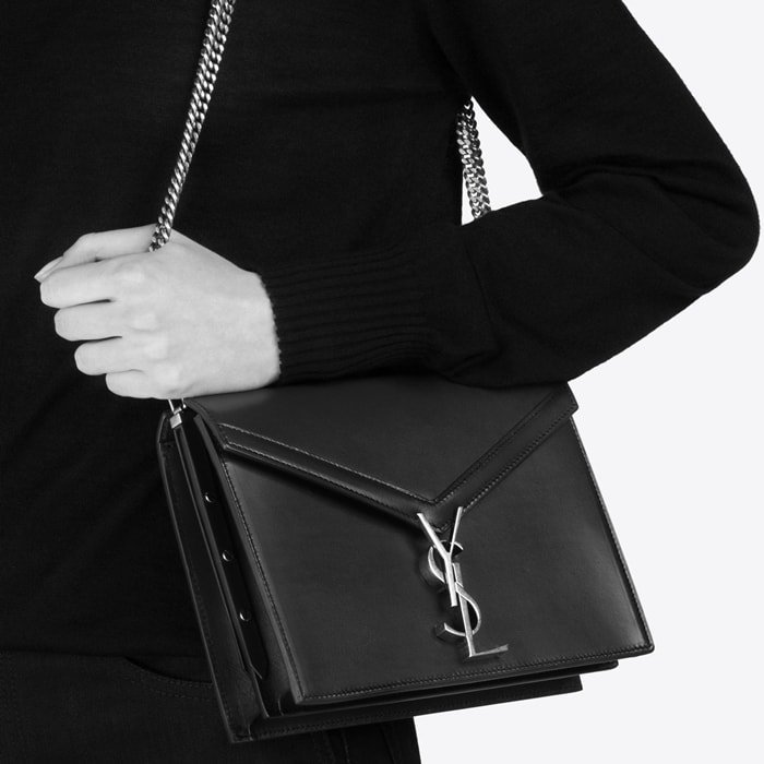 This Cassandra monogram clasp bag is crafted from calf leather and features an envelope style, a foldover top with snap closure, antique effect gold-tone hardware, a chain strap, an internal zipped pocket, two interior compartments, and a front slip pocket