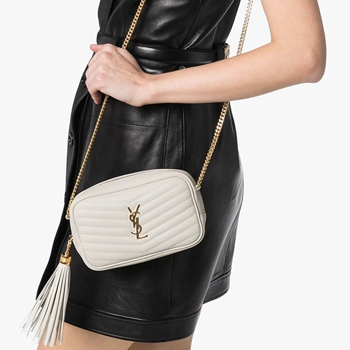 This white Saint Laurent Lou mini quilted leather camera bag has been crafted from leather and features a gold-tone chain with a leather shoulder strap, a zip at the top to fasten, a gold-tone YSL logo, and a leather side tassel
