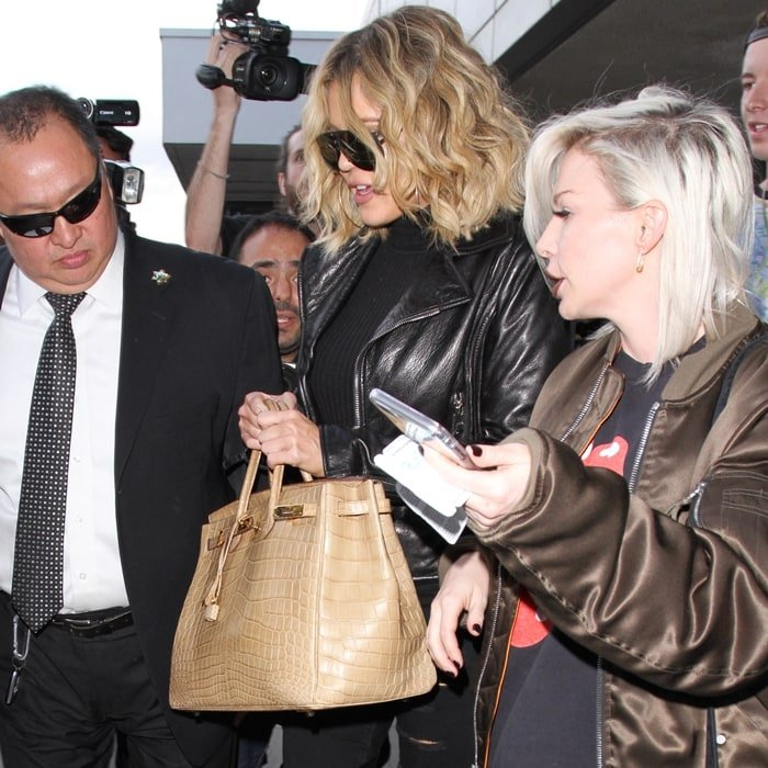 Khloé Kardashian carries a beige crocodile Hermès Birkin handbag