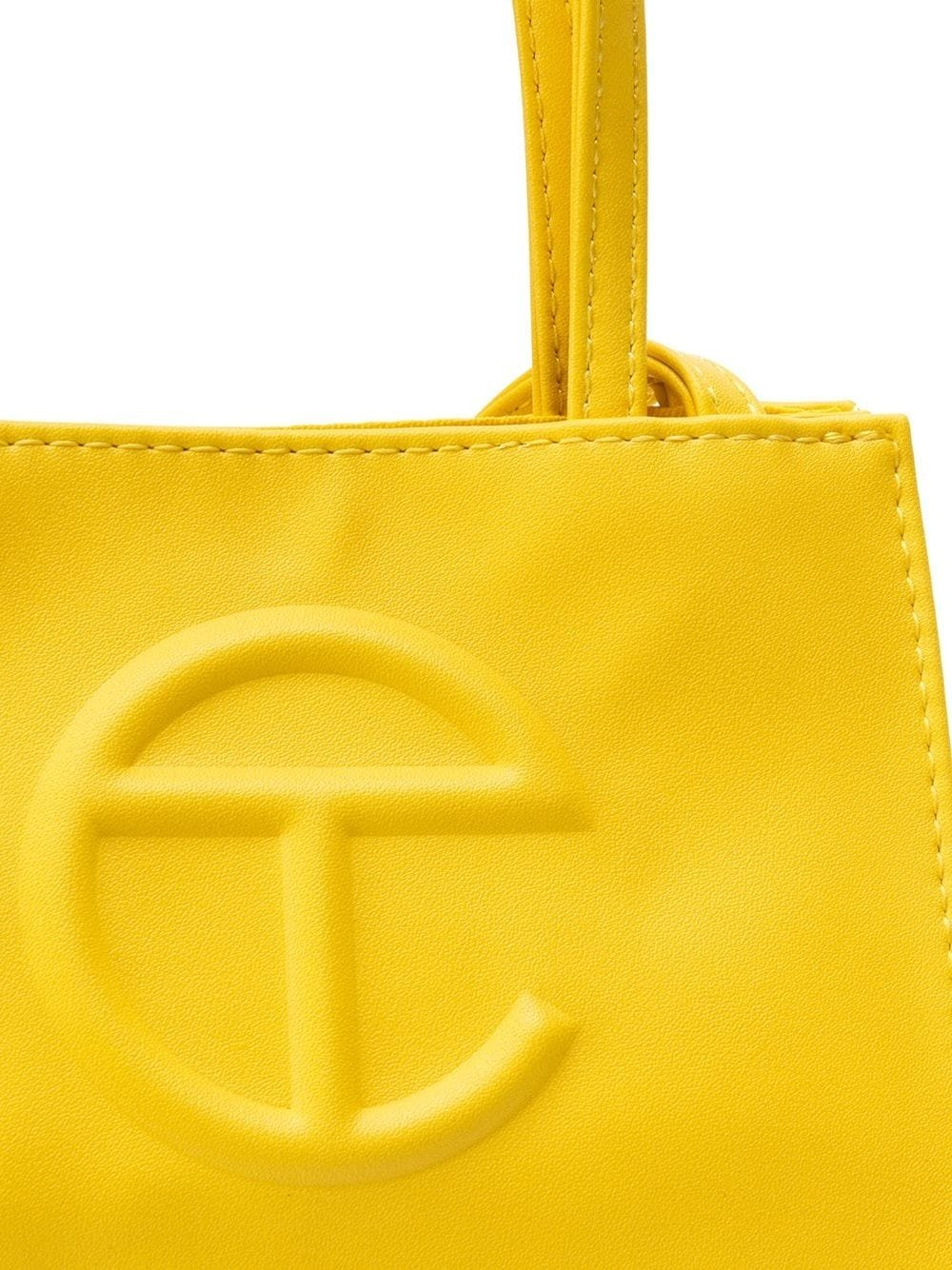 Yellow Telfar single shoulder strap tote bag with embossed front logo