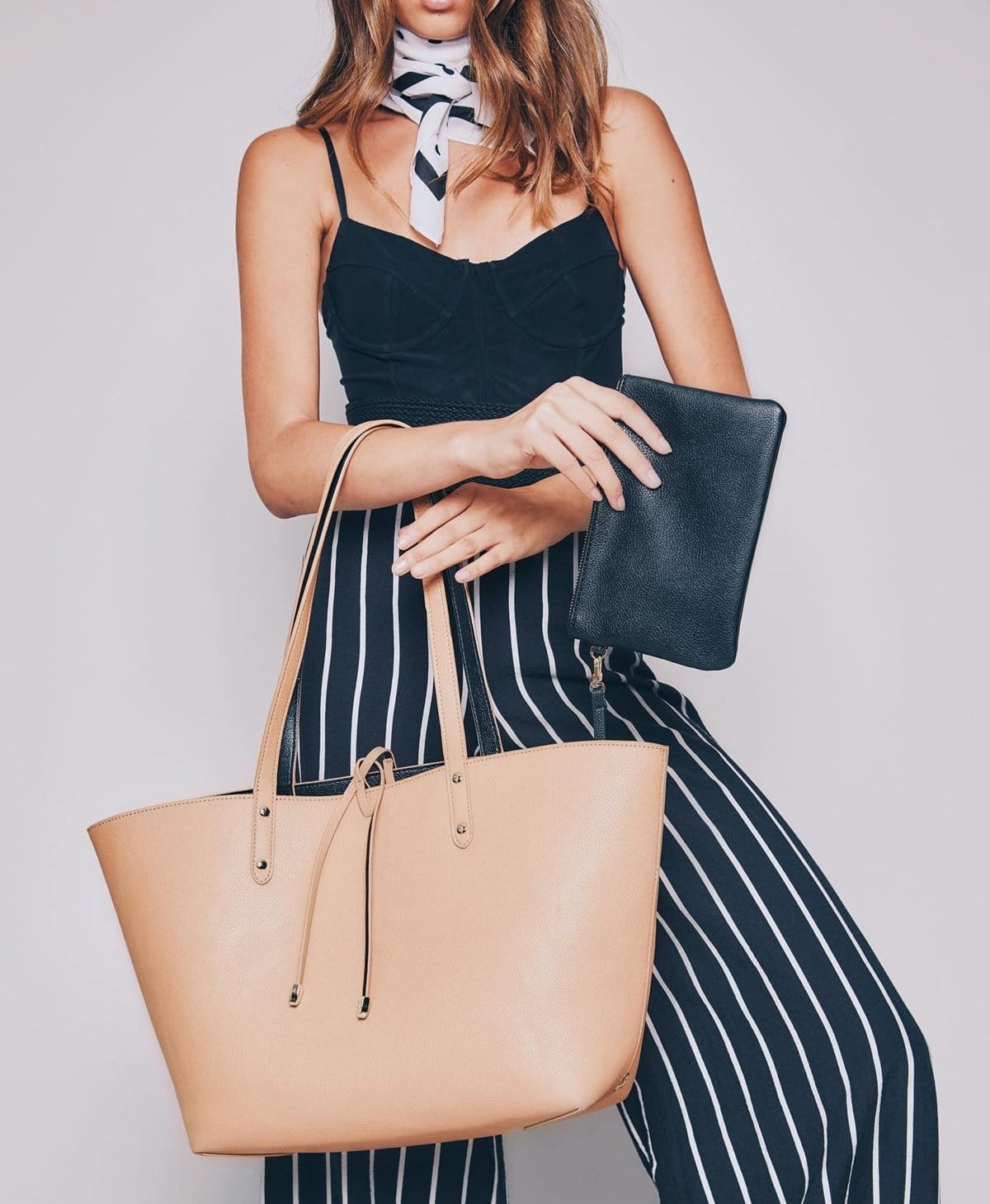 This reversible tote features a removable wristlet containing a 3000 mAh phone charging battery