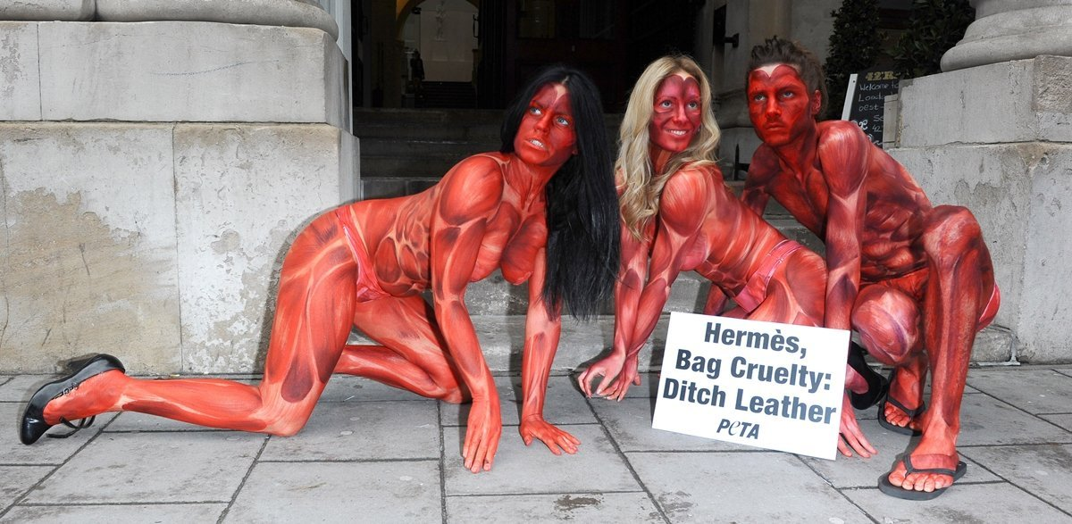"""Painted to resemble bloodied and skinned people, three models representing PETA converged outside the opening of the """"Hermes Leather Forever"""" exhibition at the Royal Academy of Arts at Burlington Gardens"""